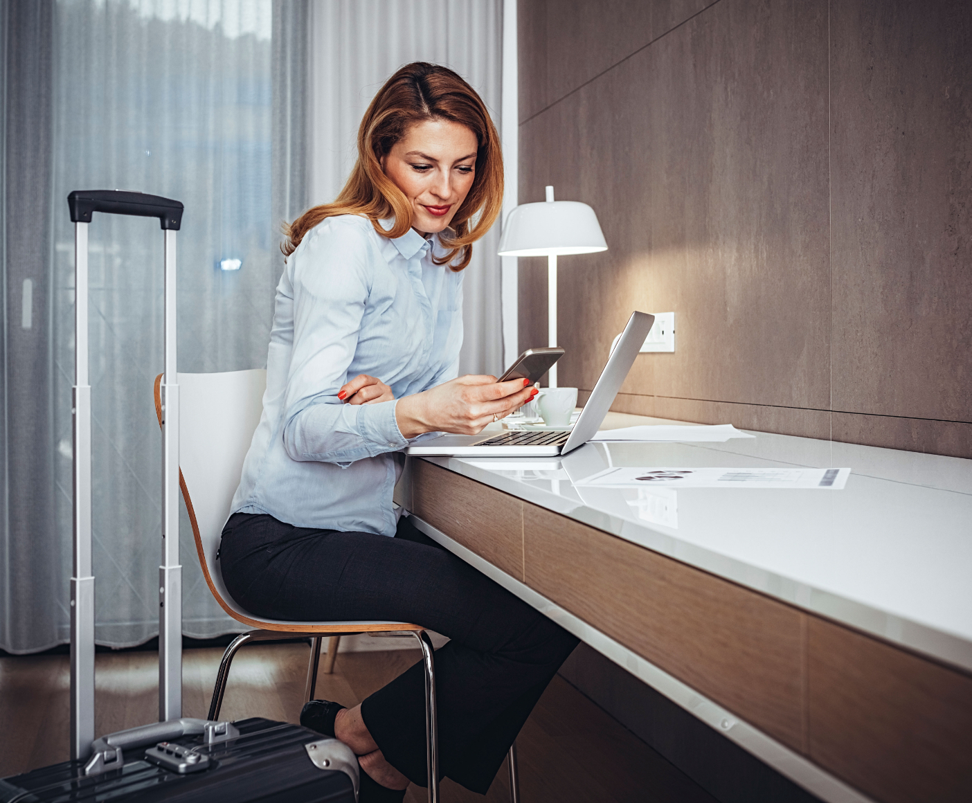 Woman looking at phone in hotel room
